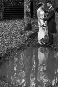 Reflection in puddle of groom holding waist of bride after their wedding at Marwell Hotel