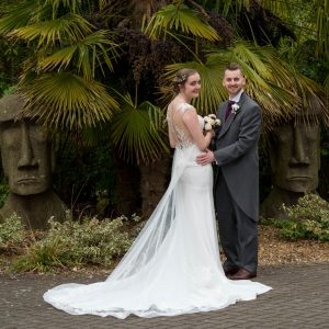 Bride and groom pose between statues at Marwell Hotel
