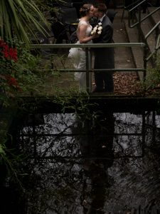 Bride and groom kiss next to pond at Marwell House