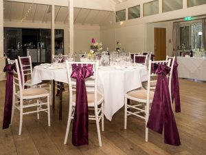 Dark burgundy ribbons adorn chairs around tables laid for wedding reception at Marwell Hotel