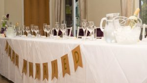 Just married banner hangs from front of top table at wedding ceception in Marwell Hotel