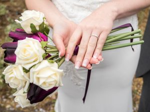 Bride shows off her ring and bouquet