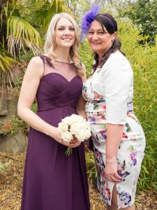 Adult bridesmaid in dark burgundy dress with her mother