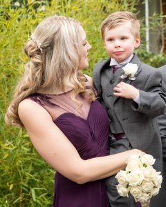 Bridesmaid  in dark burgundy dress with her son in her arms