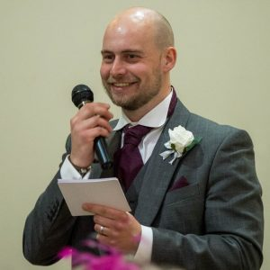 Best man smiles during his speech