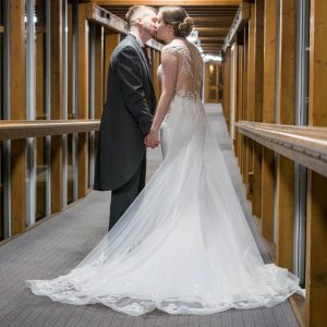 Bride and groom kiss in corridor at Marwell Hotel