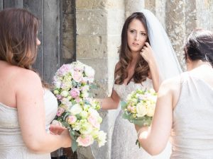 Bride and bridesmaids holding bouquets outside ancient church