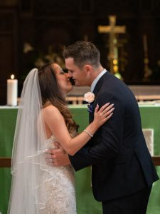 Newly-married couple about to kiss after taking marrieage voews in Portchester Church