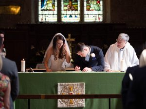 Groom signs marriage register as bride and vicar look on in Portchester Church
