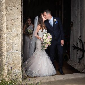 Bride and groom kiss as they leave ancient church