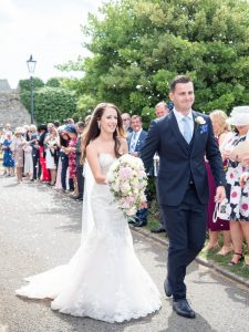 Holding her bouquet, bride walks with groom past wedding guests throwing confetti