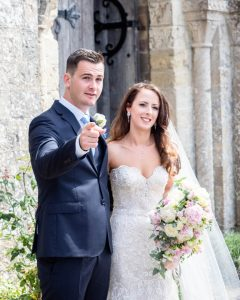 Groom points as he and bride pose for photos outside ancient church