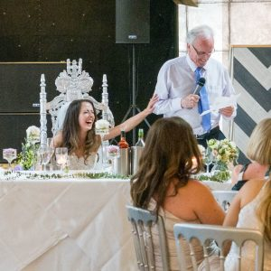 Laughing bride toutches father's arm as he delivers wedding speech at the Old Thorns Hotel, Liphook