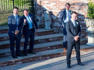 Groomsmen laugh as they pose for photos in sunshine with the groom at the Old Thorns Hotel, Liphook