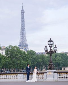 Oriental couple in wedding dress on the Pont Aleandre III with the Eiffel Tower in the background