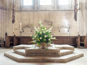 An extravagant display of white roses and lilies  in front of the font at Romsey Abbey