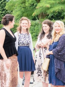Four young women in pretty outfits wait outside Romsey Abbey