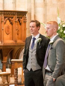 A bridegroom and a wedding usher chat before the start of a wedding service
