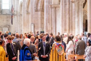A groom chats to the priest at his wedding in Romsey Abbey