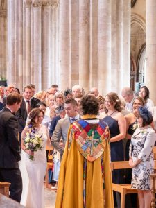 Groom, bride, her brother and the priest at a wedding service in Romsey Abbey