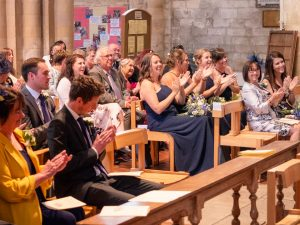 Wedding guest clap after couple get married in Romsey Abbey
