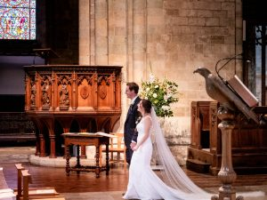 A bride and groom walk down the aisle smiling after their wedding in Romsey Abbey