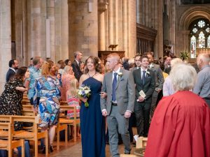 Ushers and bridesmaids walk out together after  a wedding in Romsey Abbey