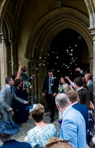 Confetti rains over a couple as they leave via the north porch at Romsey Abbey