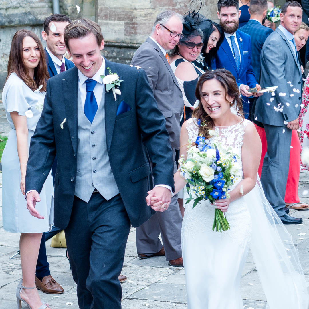 A joyful newly-married couple walk past their guests outside Romsey Abbey