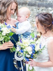 A bride admires a baby held by a bridesmaid