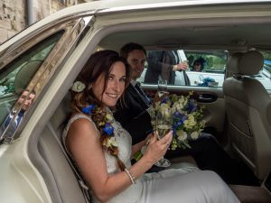 A bride and groom hold glasses of bubby in the the back of their wedding limousine