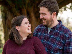 Rural Hampshire engagement shoot – man and woman gaze at each other beneath a yew tree
