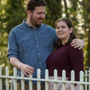 Rural Hampshire engagement shoot – man with arm around woman behind white railings