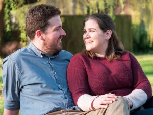 Rural Hampshire engagement shoot – couple seated on ground look lovingly at each other