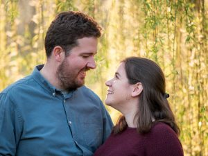 Rural Hampshire engagement shoot – backlit couple look lovingly at each other
