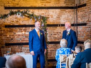 Groom and best man await bride before rustic barn wedding ceremony at The Three Tuns, Bransgore