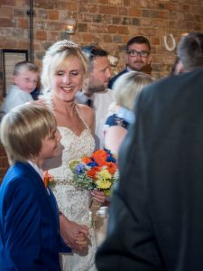 Bride walks up the aisle with her young son for rustic barn wedding ceremony at The Three Tuns, Bransgore