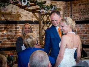 Smiling bride is given away to groom by young son during rustic barn wedding ceremony at The Three Tuns, Bransgore