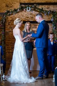 Groom receives ring from bride in rustic barn wedding ceremony at The Three Tuns, Bransgore