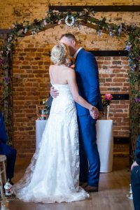 Bride and groom kiss during rustic barn wedding ceremony at The Three Tuns, Bransgore