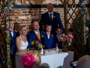 Bride. groom and family pose for photos during rustic barn wedding ceremony at The Three Tuns, Bransgore