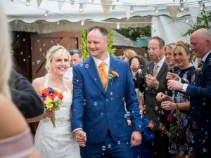 Bride and groom enjoy bubble confetti after rustic barn wedding ceremony at The Three Tuns, Bransgore