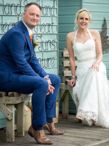 Bride and groom seated in front of chalets at the Three Tuns, Bransgore
