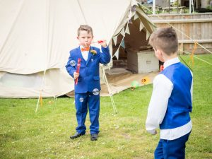 Page boys blow bubbles after rustic barn wedding ceremony at the Three Tuns, Breansgore