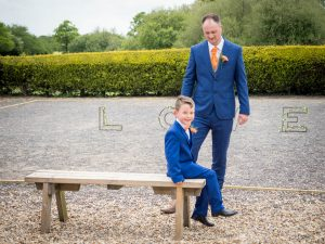 Groom and son in matching blue suits pase after rustic barn wedding ceremony at the Three Tuns, Breansgore