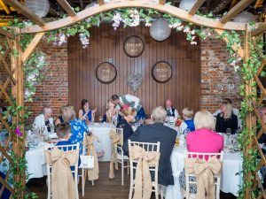 Groom gkisses bride during rustic barn wedding reception at the Three Tuns, Bransgore