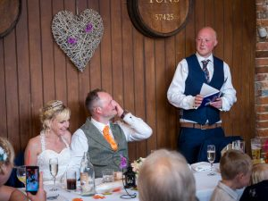 Best man makes speech during rustic barn wedding reception at the Three Tuns, Bransgore