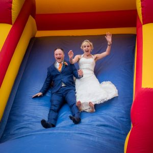 Bride and groom on bouncy castle slide at The Three Tuns, Bransgore