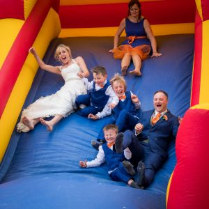Bride, groom and family on bouncy castle slide at The Three Tuns, Bransgore