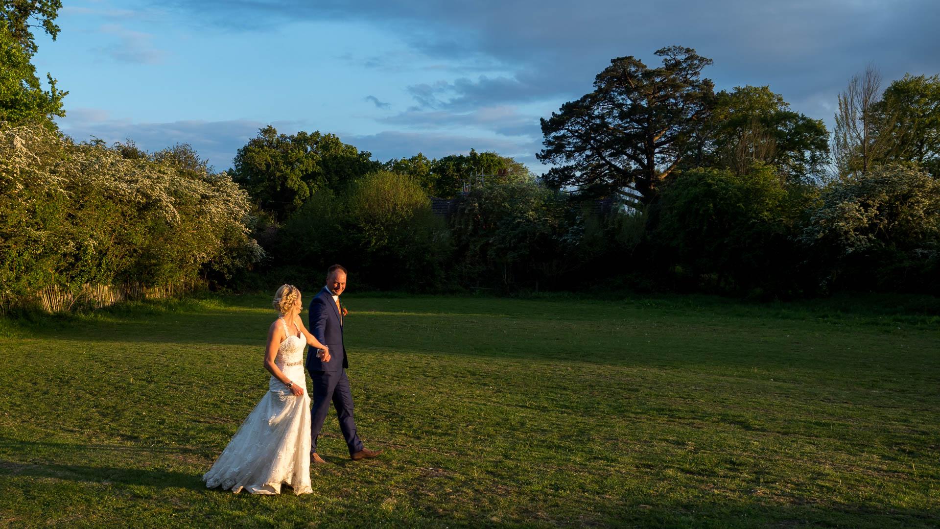 Bride and groom walk across field in spring evening sunshine